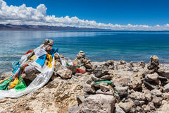 Marnyi stone with sutra streamers on the lakeside of Namtso Royalty Free Stock Photos