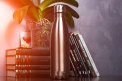 Maro de bouteille thermo de couleur au-dessus du fond des livres et de la fleur verte Avec l'effet de lumière du soleil photos libres de droits