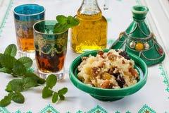 Marockansk couscous med torkat - frukt och muttrar i tagÃne Arkivfoto