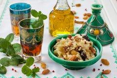 Marockansk couscous med torkat - frukt och muttrar i tagÃne Arkivfoton