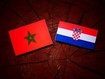 Marockansk flagga med den kroatiska flaggan på en isolerad trädstubbe Fotografering för Bildbyråer