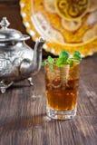 Marockanskt te med mintkaramellen, järnkokkärlet och den traditionella maträtten Arkivbilder