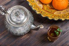 Marockanskt te med mintkaramellen, järnkokkärlet och den traditionella maträtten Royaltyfri Bild
