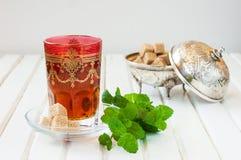 Marockanskt te med mintkaramellen och socker i ett exponeringsglas på en vit tabell med en kokkärl Royaltyfria Bilder