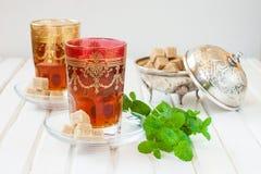 Marockanskt te med mintkaramellen och socker i ett exponeringsglas på en vit tabell med en kokkärl Arkivbild