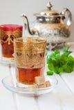 Marockanskt te med mintkaramellen och socker i ett exponeringsglas på en vit tabell med en kokkärl Royaltyfri Foto