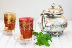 Marockanskt te med mintkaramellen och socker i ett exponeringsglas på en vit tabell med en kokkärl Arkivfoto