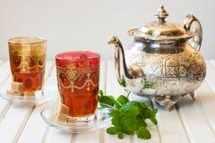 Marockanskt te med mintkaramellen och socker i ett exponeringsglas på en vit tabell med en kokkärl Fotografering för Bildbyråer