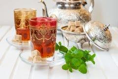 Marockanskt te med mintkaramellen och socker i ett exponeringsglas på en vit tabell med en kokkärl Arkivbilder