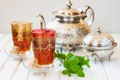 Marockanskt te med mintkaramellen och socker i ett exponeringsglas på en vit tabell med en kokkärl Royaltyfri Fotografi