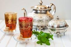 Marockanskt te med mintkaramellen och socker i ett exponeringsglas på en vit tabell med en kokkärl Royaltyfria Foton