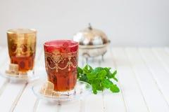 Marockanskt te med mintkaramellen och socker i ett exponeringsglas på en vit tabell med en kokkärl Royaltyfri Bild