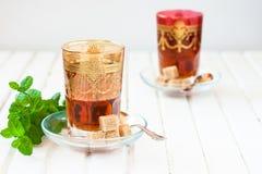 Marokańska herbata z mennicą i cukierem w szkle na białym stole z czajnikiem Zdjęcie Stock