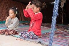 Marokkaanse Berber-meisjes die in een tent in de Sahara zitten stock fotografie