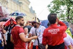 Marokkaanse voetbalventilators in de regen dichtbij GOM in Moskou stock foto's