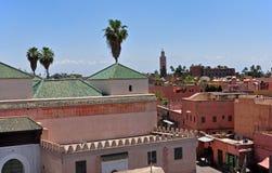Marokkanische Stadt von Marrakesch mit Moschee und Gebirgszug hohem Atlas im Hintergrund Lizenzfreie Stockfotos