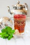 Marokkanischer Tee mit Minze und Zucker in einem Glas auf einer weißen Tabelle mit einem Kessel Stockfotos