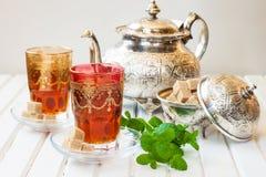Marokkanischer Tee mit Minze und Zucker in einem Glas auf einer weißen Tabelle mit einem Kessel Stockbilder