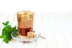 Marokkanischer Tee mit Minze und Zucker in einem Glas auf einer weißen Tabelle mit einem Kessel Lizenzfreies Stockbild