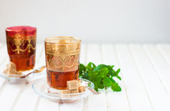 Marokkanischer Tee mit Minze und Zucker in einem Glas auf einer weißen Tabelle mit einem Kessel Lizenzfreie Stockfotografie