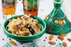 Marokkanisches Kuskus mit Trockenfrüchten und Nüssen im tagÃne Stockbilder