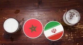 Marokko versus De Onderleggers voor glazen van Iran bij de bar met pinten van bier Stock Fotografie