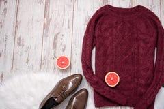 Maroon связанный свитер, коричневые ботинки лакированной кожи, отрезанные половины грейпфрута Деревянная предпосылка, космос для  Стоковые Фото