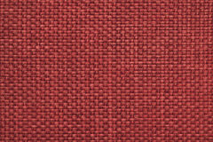 Maroon background with braided checkered pattern, closeup. Texture of the weaving fabric, macro. Stock Photography