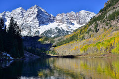 Maroon Bells during foliage season with snow covered mountains and yellow aspen reflecting in the lake Stock Photography