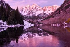 Maroon Bells and Maroon Lake at sunrise. Maroon Bells and Maroon Lake with reflection of rocks and mountains in snow at sunrise around at autumn in Colorado Stock Photo