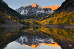 Maroon bells peak sunrise Aspen Fall Colorado. Beautiful sunrise touches Maroon bells peak at Maroon lake, Aspen, Colorado. Fall color of Aspen and reflection of royalty free stock photography