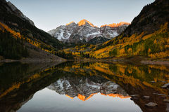 Maroon bells peak sunrise Aspen Fall Colorado. Beautiful sunrise touches Maroon bells peak at Maroon lake, Aspen, Colorado. Fall color of Aspen and reflection of royalty free stock images