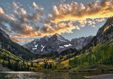 Maroon Bells peaks and fall colors in the Rocky Mountain National Park. The Maroon Bells peaks at sunset, dusted with snow, surrounded by autumn colors are Stock Images