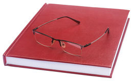 Maroon colored thesis paper with spectacles Stock Image