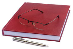 Maroon colored thesis paper with spectacles Stock Photo