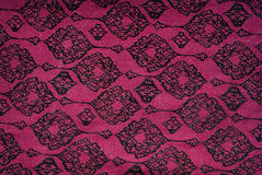 Maroon fabric with black patterns background Stock Photo
