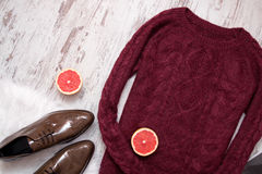 Maroon knitted sweater, brown patent leather shoes, cut grapefruit halves. Wooden background. Fashion concept. Stock Image