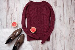 Maroon knitted sweater, brown patent leather shoes, cut grapefruit halves. Wooden background, space for text. Fashion concept. top Stock Photography