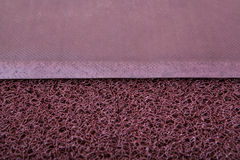 Maroon mat for shoes to enter the room. Cleaning and fixing the texture closeup Stock Photo
