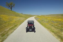 A maroon Model T driving down a scenic road surrounded by spring flowers off of Route 58, Shell Road, CA Royalty Free Stock Image