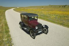 A maroon Model T driving down a scenic road surrounded by spring flowers off of Route 58, Shell Road, CA Royalty Free Stock Photo