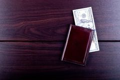 Maroon purse with hundred dollar bills on a burgundy table, top Royalty Free Stock Photo