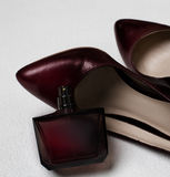 Maroon shoes and perfume Stock Photos