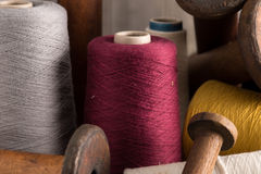 Maroon Thread Alongside Other Colour Thread. A spool of maroon thread in the center along side other color spools of thread and empty wooden spools stock photography