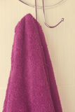 Maroon towel hanging on a hook Royalty Free Stock Photos