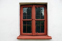 Maroon window in a white wall. Old maroon window in a white wall in a rural area stock image