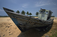 Marooned. An old wooden fishing boat left high and dry on the beach royalty free stock image