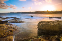 Bondi beach sea coast long exposure at sunset. Long exposure of sea coast.  The water looks like milk on the big rocks standing.  The sky has a beautiful golden Royalty Free Stock Photography