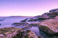 Maroubra beach sea coast long exposure at sunset. Long exposure of sea coast.  The water looks like milk on the big rocks standing.  The sky has a purple Stock Image