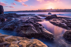 Bondi beach sea coast long exposure at sunset. Long exposure of sea coast.  The water looks like milk on the big rocks standing.  The sky has a purple colour Stock Photography
